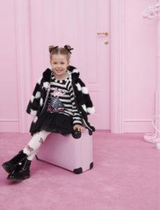 bambina sorridente seduta su valigia con abiti bianco e nero in una stanza completamente rosa