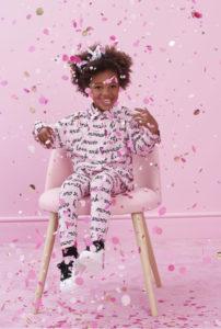 Bambina di pelle nera sorridente seduta su una sedia rosa in una stanza rosa con coriandoli rosa